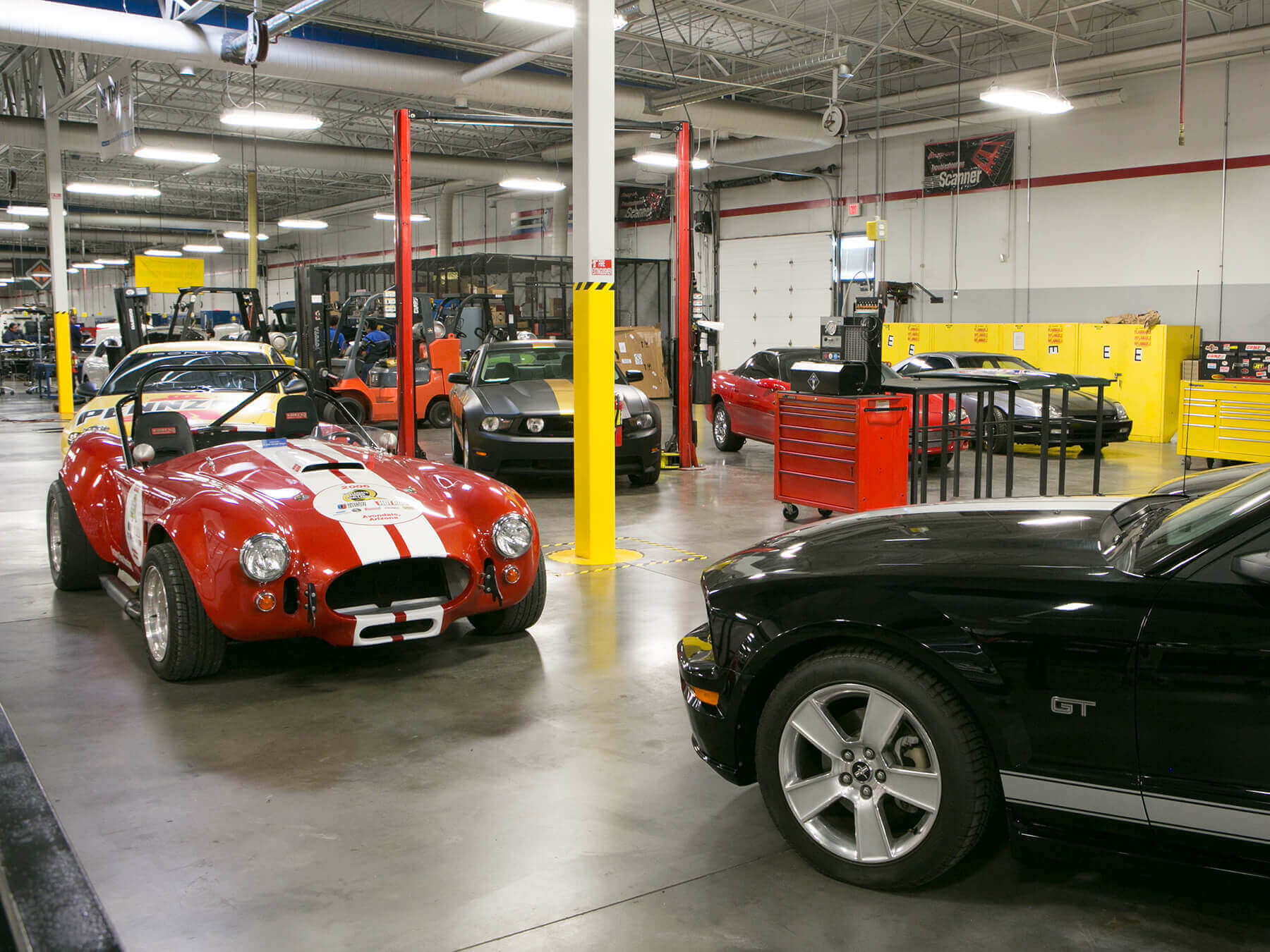Red sports car with a black mustang GT in the auto lab at Avondale Campus