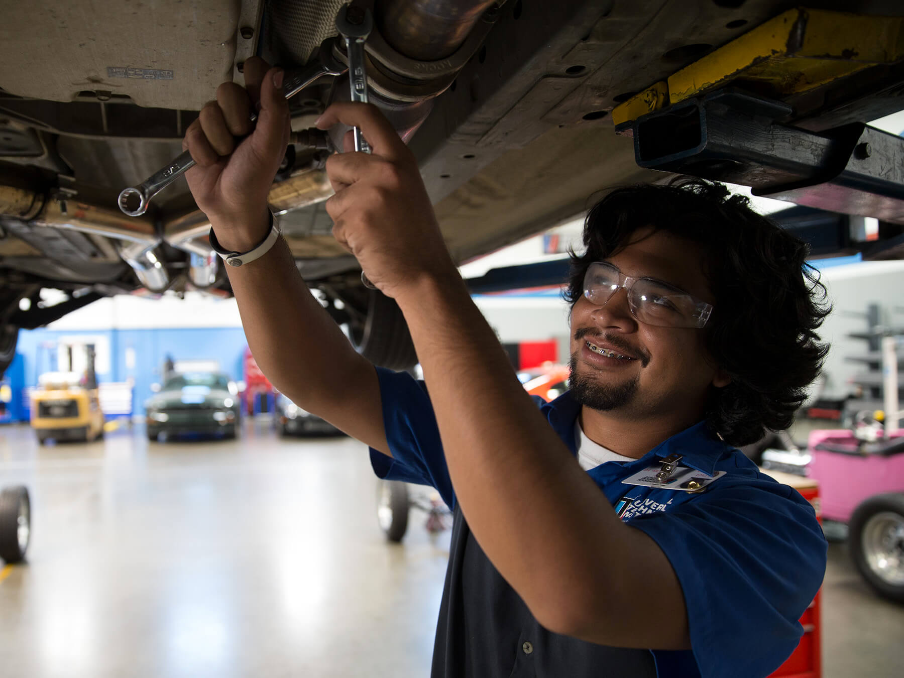 UTI student smiling while working underneath a car