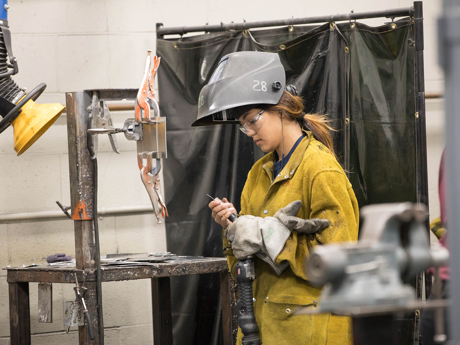Female welding student looking down at her tools in the CRRT lab at Sacramento campus