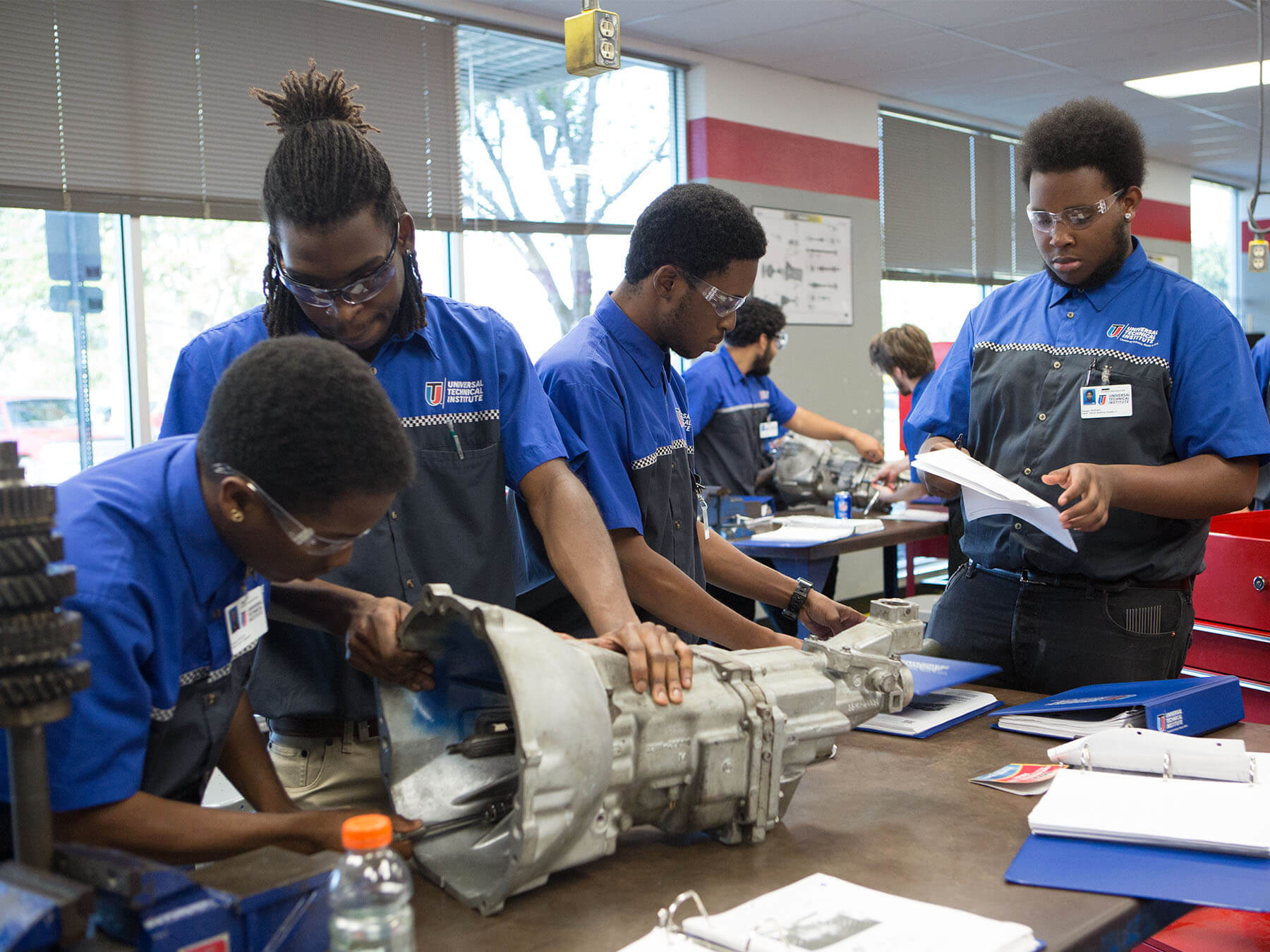 UTI students working on an engine in the classroom