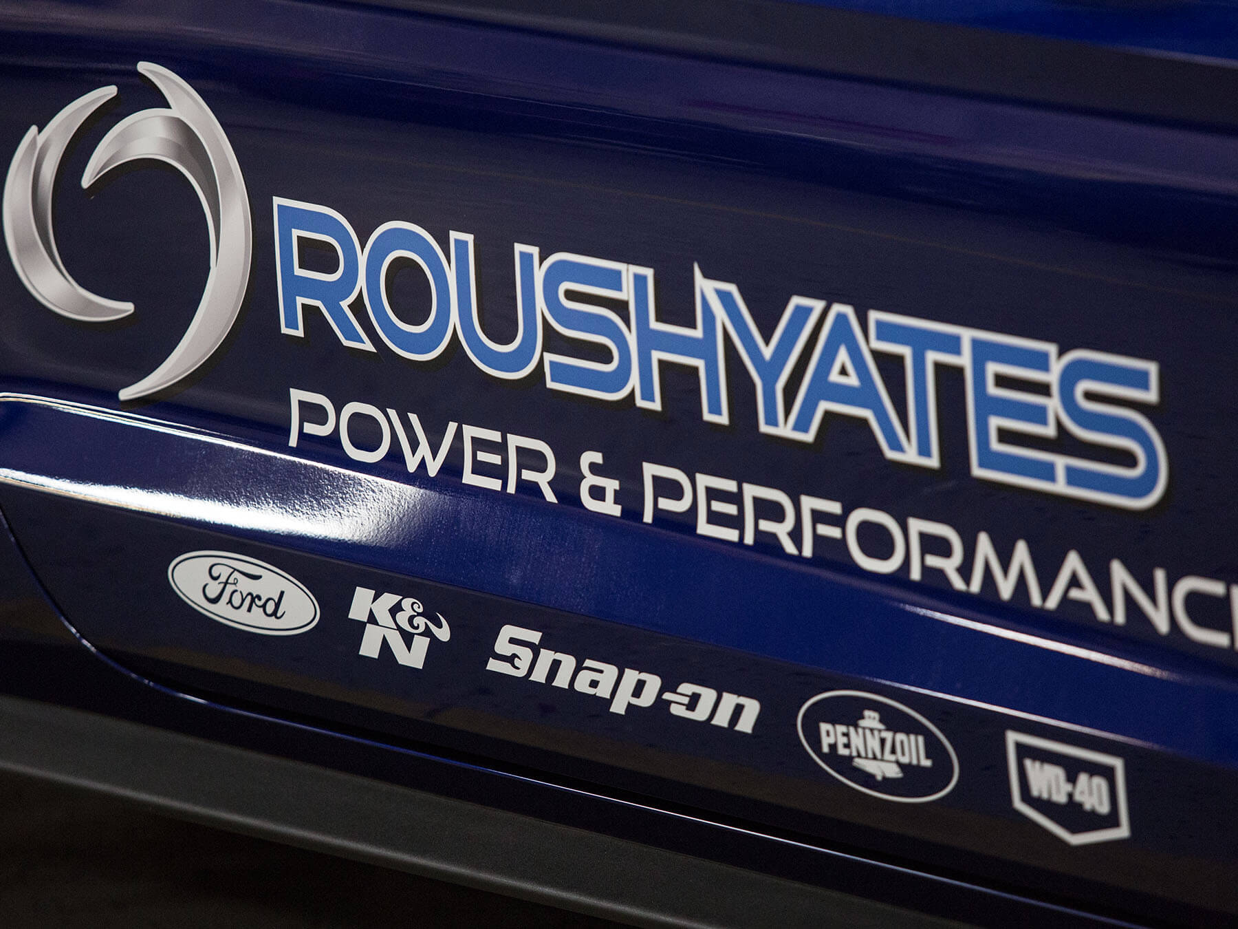 Close up on the blue roushyates logo
