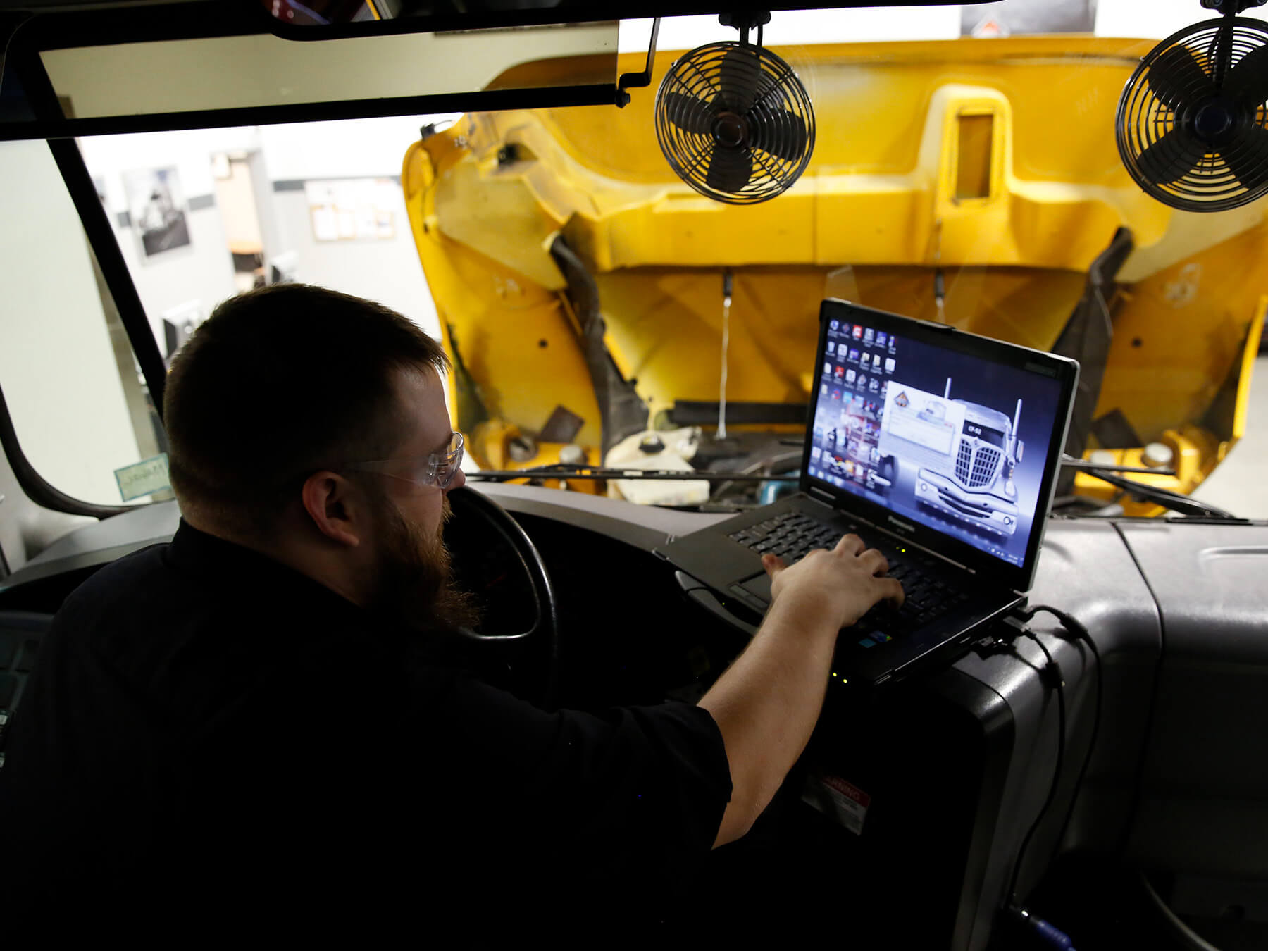 UTI student working inside of a diesel truck on a laptop