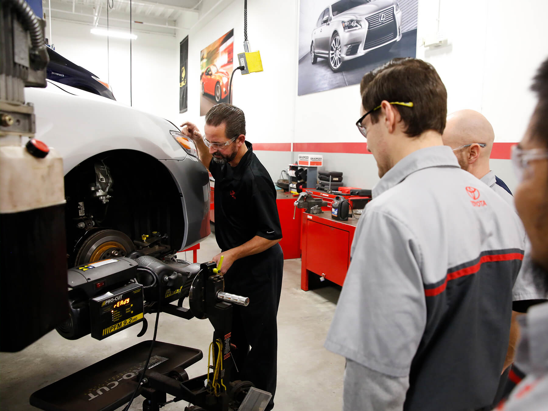 UTI students and instructor working on a tire in the Toyota auto lab
