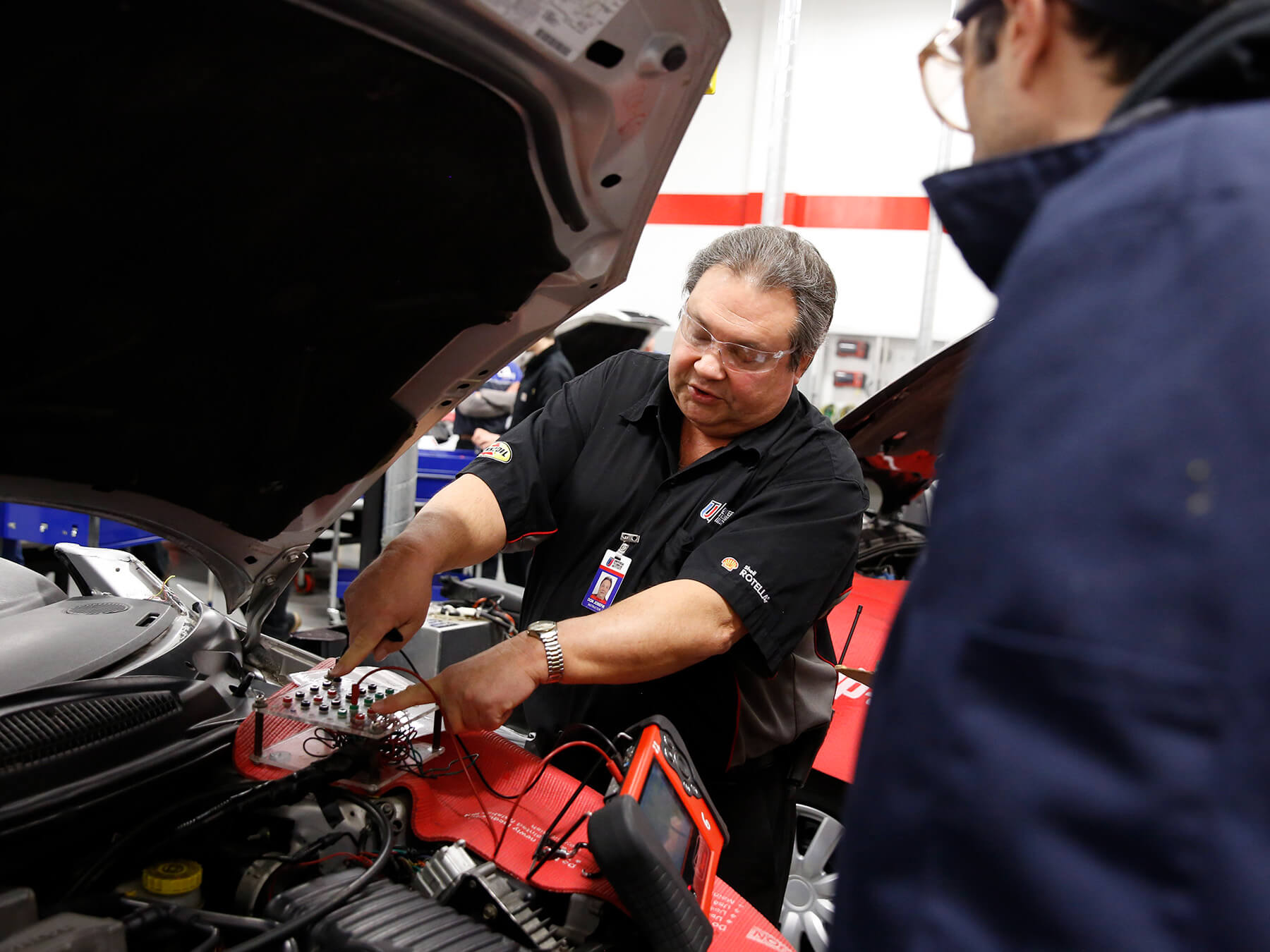 UTI students and instructor working under the hood in the auto lab