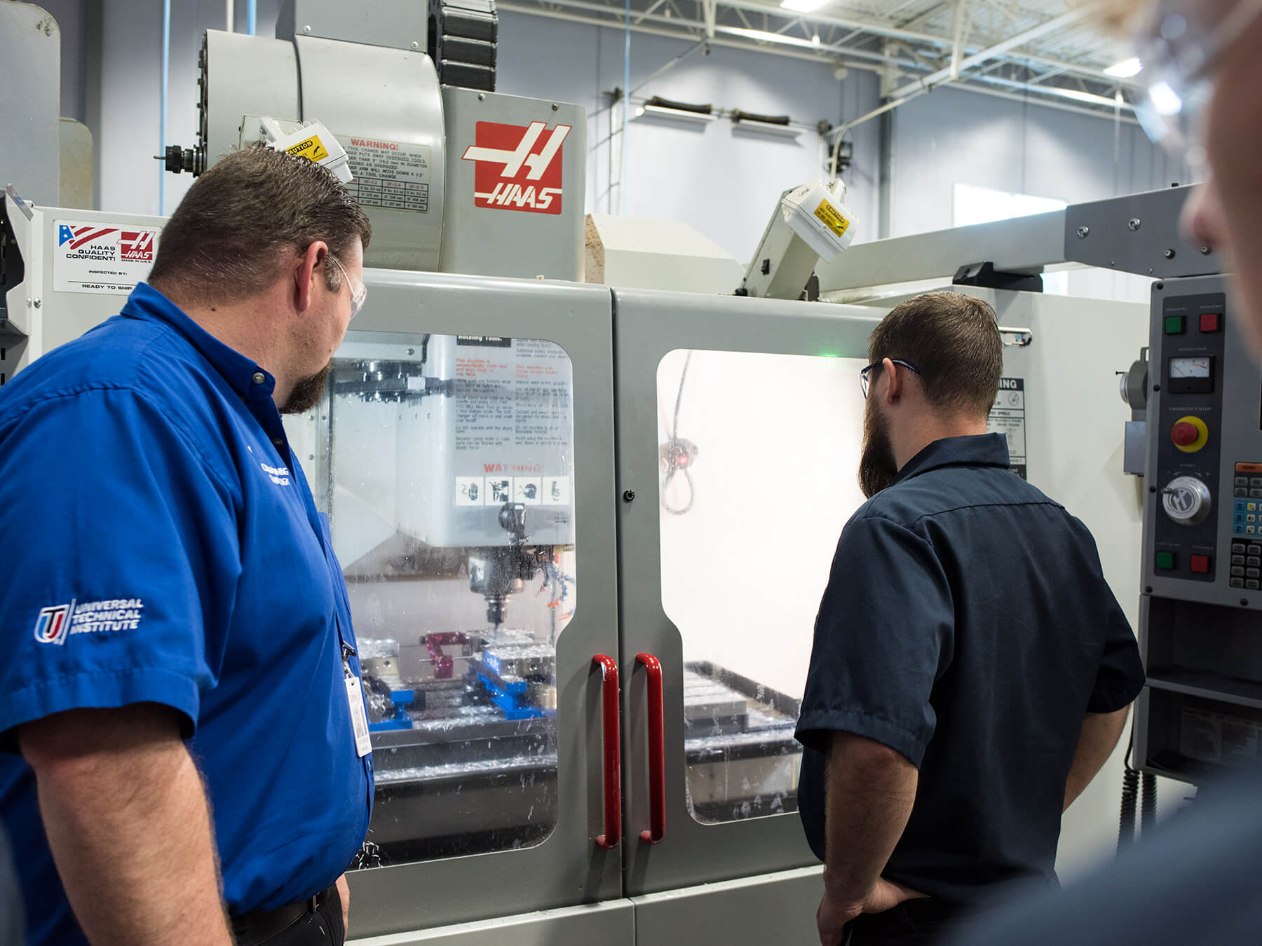 Instructor and student looking at the CNC machine at Mooresville campus