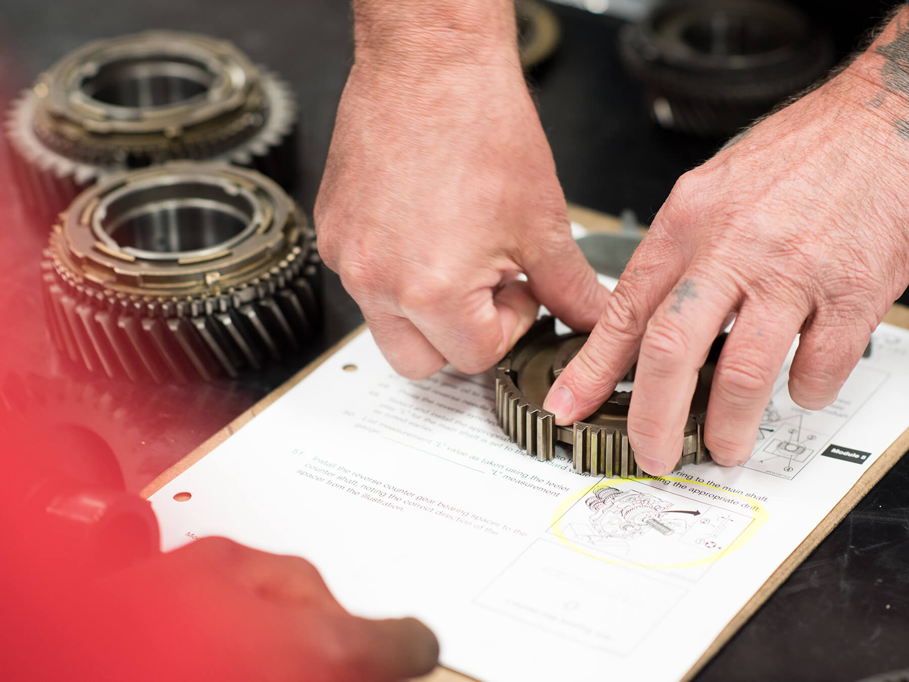 Photo of hands working on a gear in the Nissan lab at Mooresville campus
