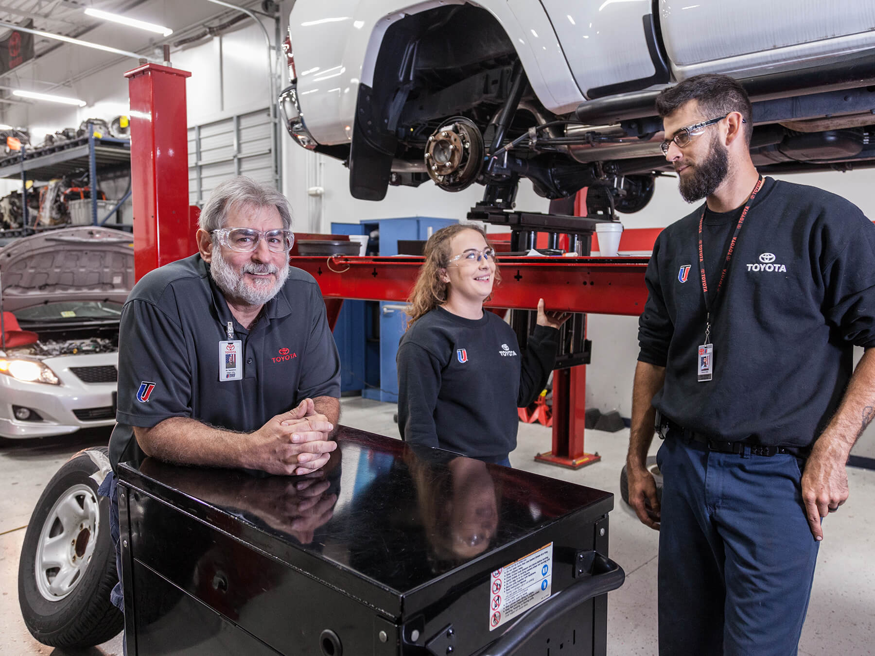 Students and Instructor smiling near a car on a lift  in the Toyota lab at the Exton campus