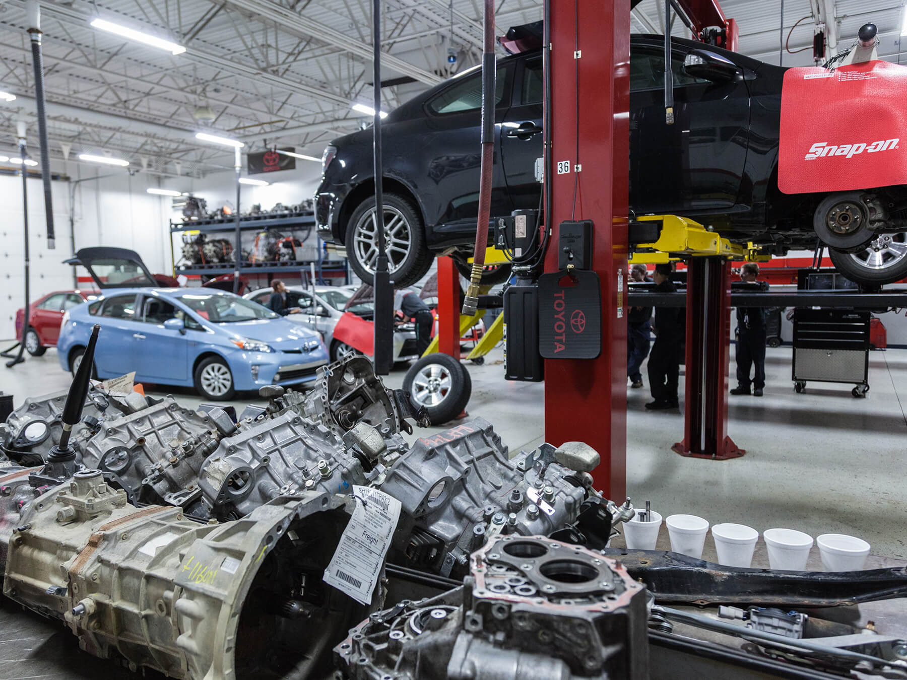 Photo of engine parts and Toyota cars on lifts in the Toyota lab at the Exton campus