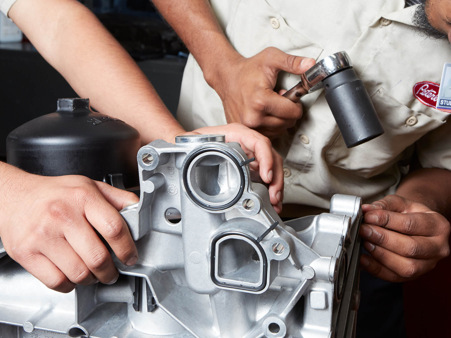 Close up of student hands working on an engine at the Dallas campus