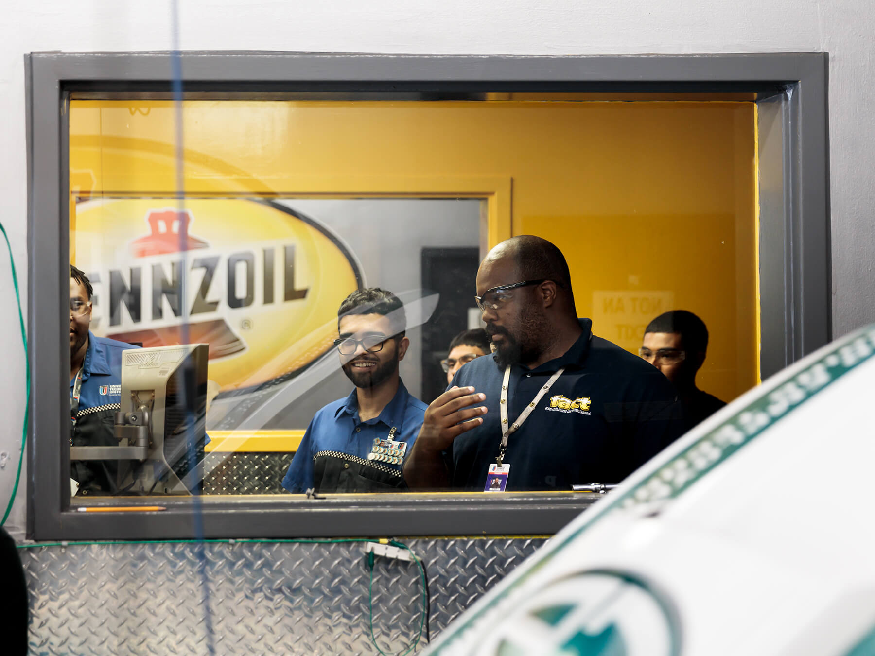 Instructor and students looking from behind glass in the DYNO lab  at the Houston campus