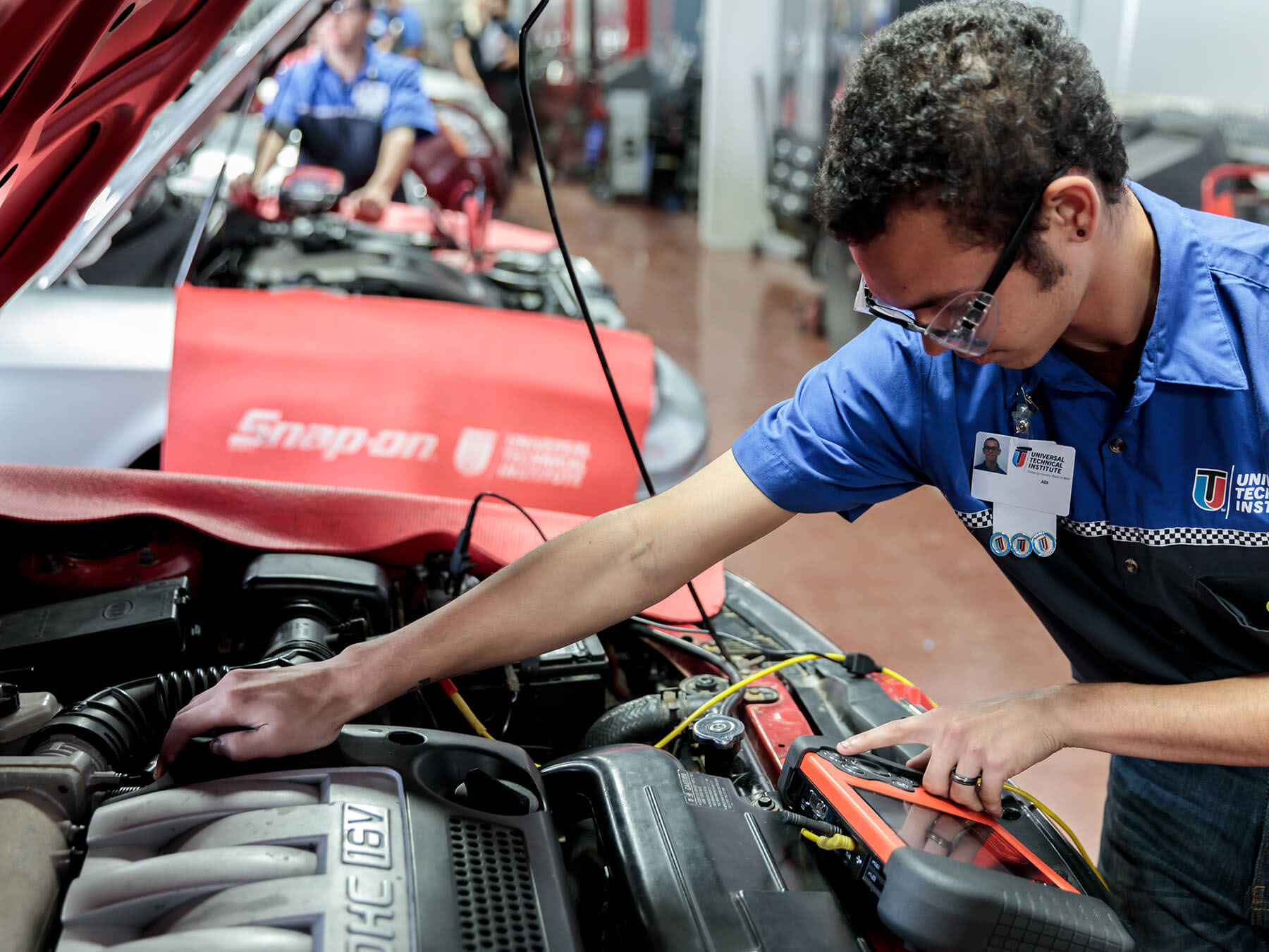 Student working under the hood with a snap-on tool in the Auto lab at the Houston campus