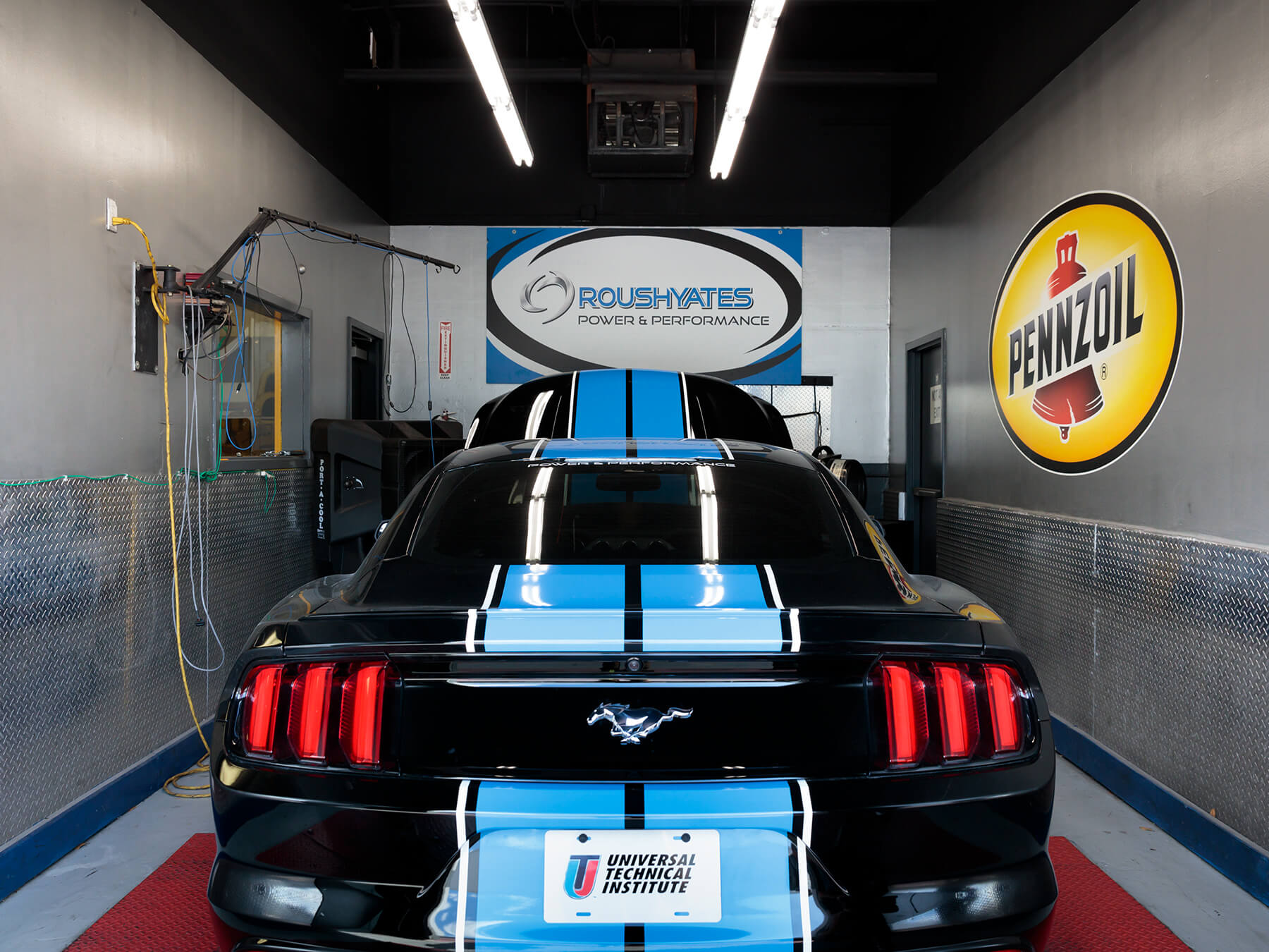 Black mustang with Blue Pinstripes in the DYNO lab at the Houston campus