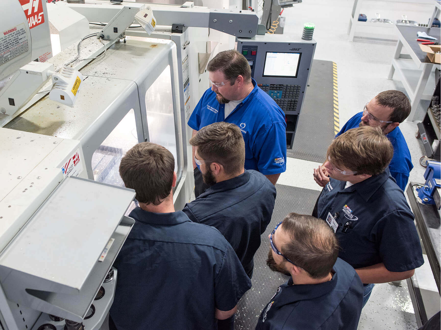 Overhead photo of Instructor and students looking into the CNC machine