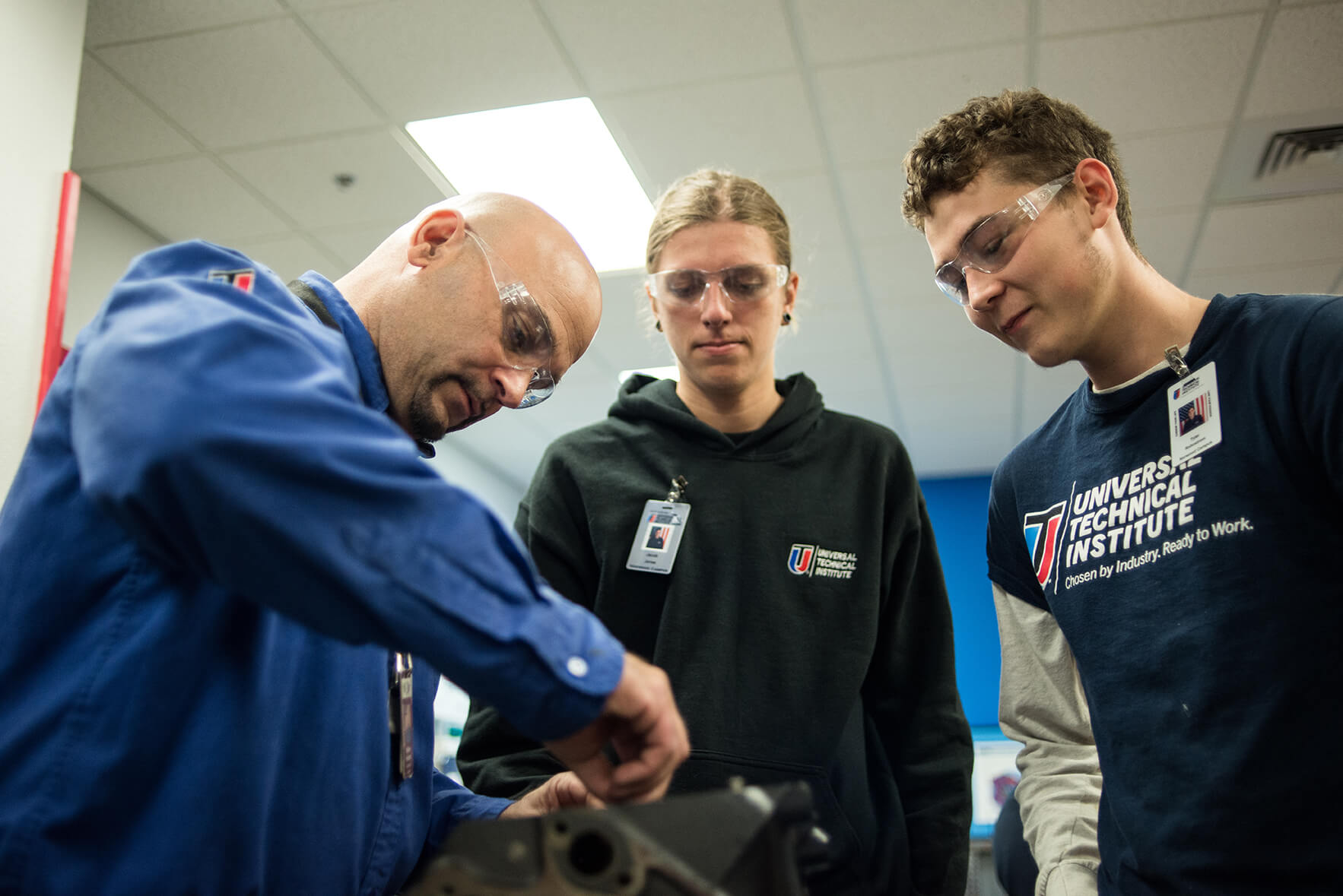 An instructor with two students on automotive components at UTI's Ignite program