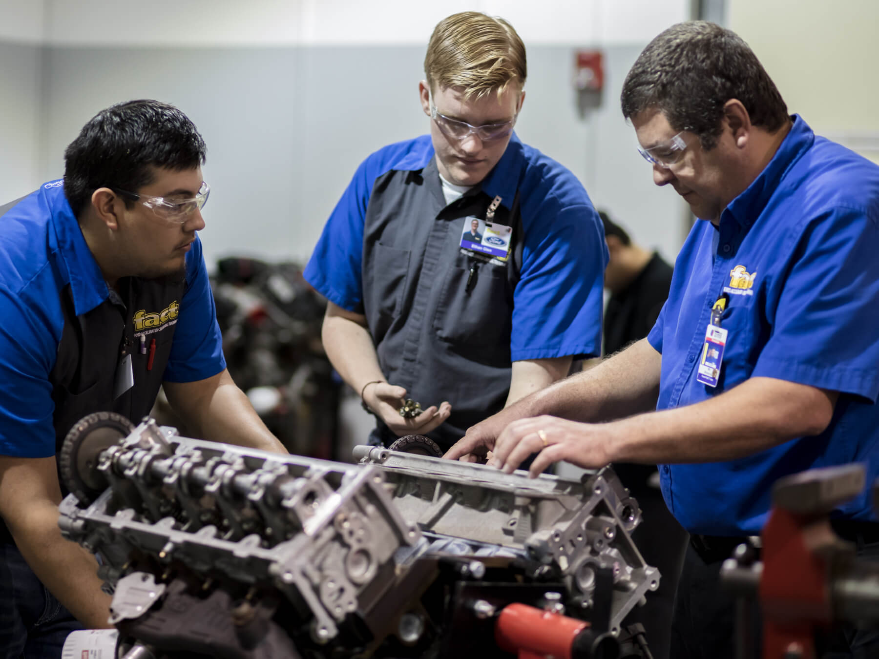 UTI instructor and students working on an engine in the ford auto lab