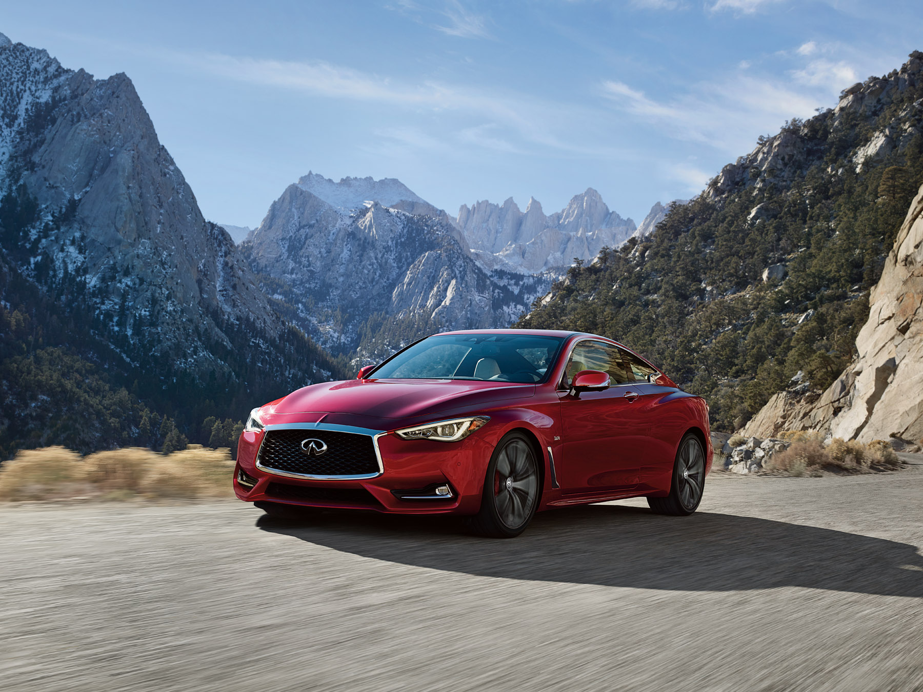 Red Infiniti Q60 driving on the mountain side