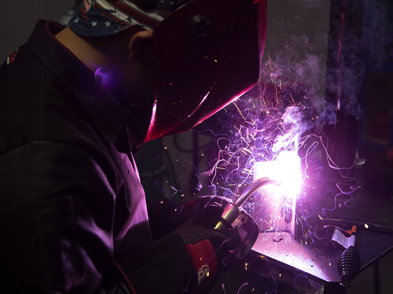 Over the shoulder photo of a welding student welding creating a purple flame
